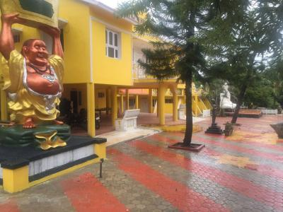 laughing buddha statue with building view